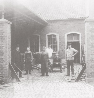 'Alte Schmiede' (old blacksmith's). The two bricked gate posts are still visible today. The left half of the yard was covered by a roof, this is where the shodding stall stood and is where the horses were shod. The workplace was expanded in the 1920's, as is still visible today. From left to right: Heinrich Belting (Weeze's coppersmith and plumber), two unknown journeymen (trainees), Theodor Weigand (master painter), Heinrich Verhülsdonk (owner of the pub on Kirchplatz/corner Kirchplatz/corner Loëstrasse) and blacksmith Theodor Kerns, postcard-view from around 1910.
